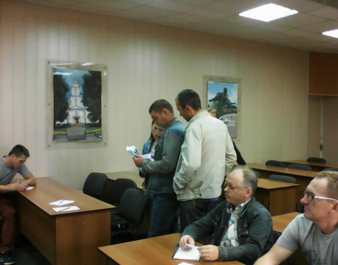 Пришедшие на встречу просматривают фотоальбом с мест ДТП - зрелище поучительное, но не для слабонервных
