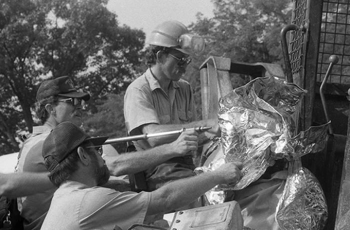 """God Bless America (1990). Лесная служба США использует автоген, чтобы отсоединить демонстранта от лесозаготовительной техники. Им пришлось обернуть голову этого человека алюминиевым щитом. Пока они резали замок, демонстрант пел """"Боже, благослови Америку"""". Фото Orin Langelle"""