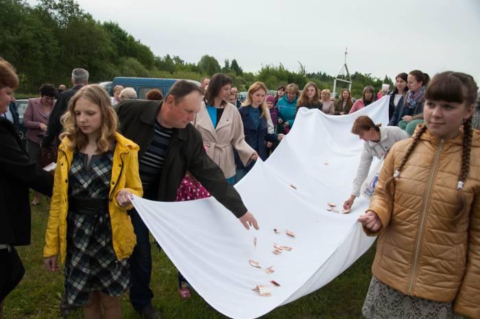 Собравшиеся на кладбище тоже кладут жертву на полотно. Фото Анастасии Вереск